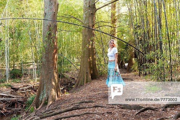 zwischen  inmitten  mitten  Spazierstock  Stock  blond  Frau  Fröhlichkeit  gehen  Rock  weiß  hoch  oben  Garten  Kleidung  Bambus  alt  Jahr