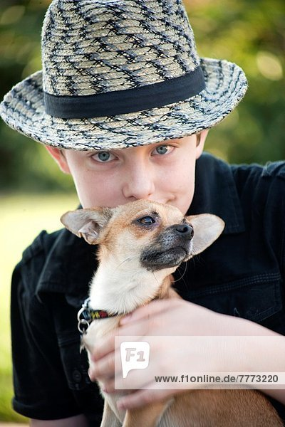 young boy holding his Chihuahua on his lap