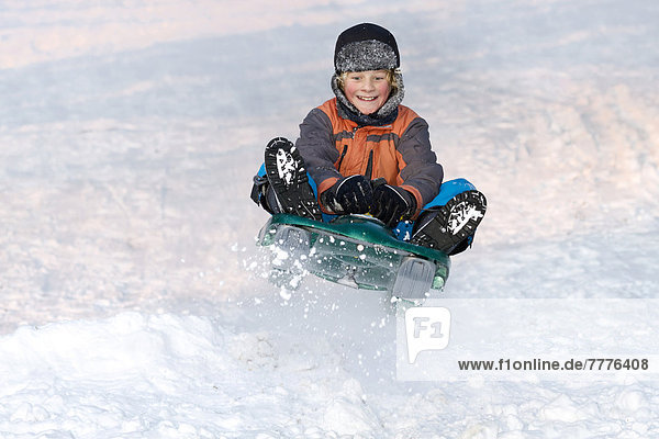 Boy jumping with a sledge