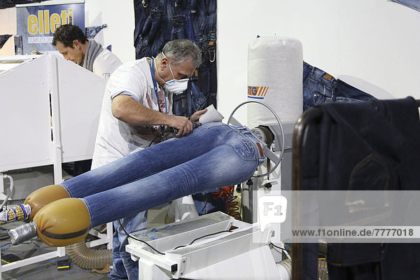 'Jean production at the stand of ''Pepe Jeans''  the jeans getting fashionable wear and tear markings  Bread and Butter Winter 2013  fashion fair in the grounds of the former Berlin-Tempelhof airport '