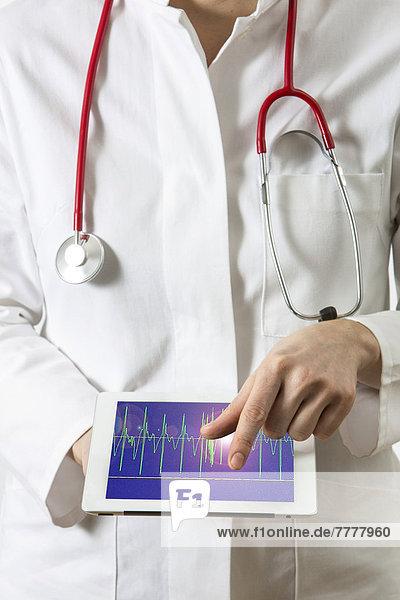 Ärztin hält einen Tablet-Computer  iPad  darauf EKG-Kurve