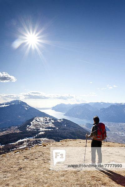 Wanderer beim Aufstieg zum Monte Stivo  hinten der Gardasee mit dem Dorf Riva