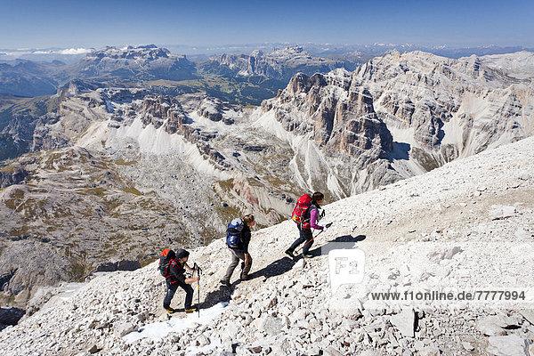 Bergsteiger beim Aufstieg auf die Tofana di Rozes über die Via ferrata Giovanni Lipella  hinten der Sellastock und das Grödnerjoch  Dolomiten