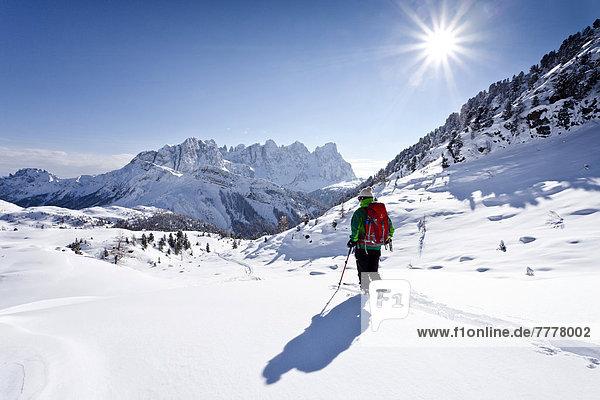 Skitourengeher bei der Abfahrt vom Juribrutto  hinten die Palagruppe  unten der Passo Valles