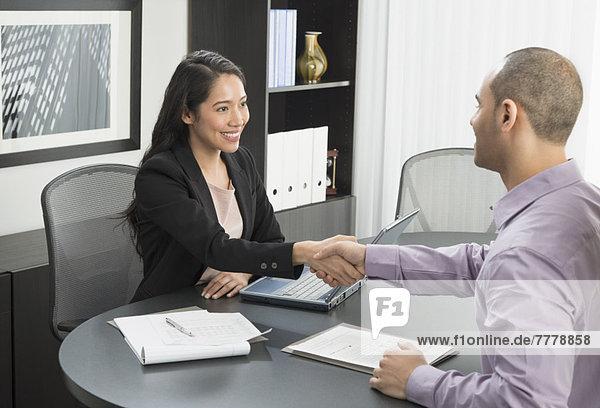 Mann und Frau Händeschütteln in office