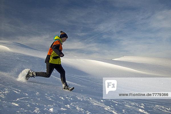 Zwölfjähriger Junge rennt durch den Schnee