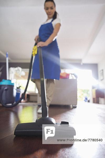Frau saugt Wohnzimmerboden ab