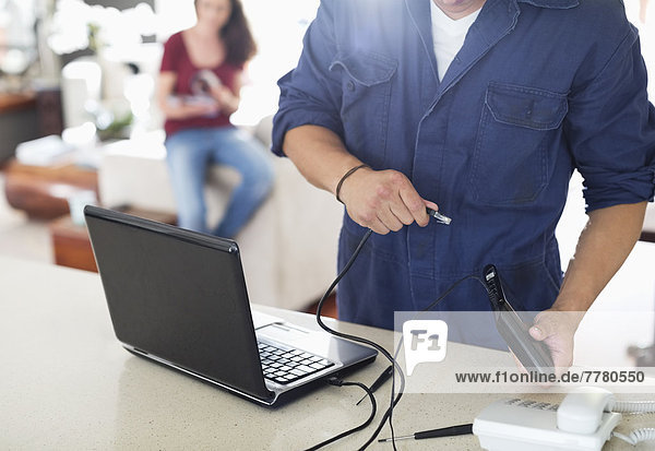 Electrician using laptop in home
