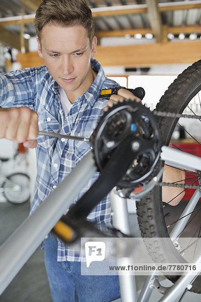 Mann arbeitet auf dem Fahrrad in der Werkstatt