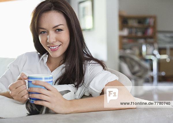 Lächelnde Frau trinkt eine Tasse Kaffee