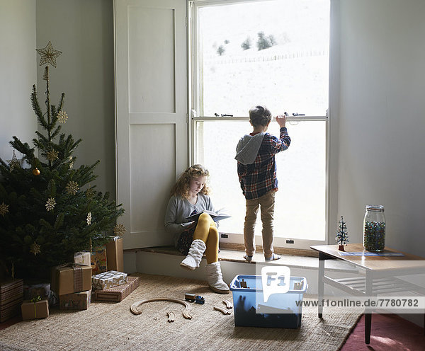 Children in living room with Christmas tree