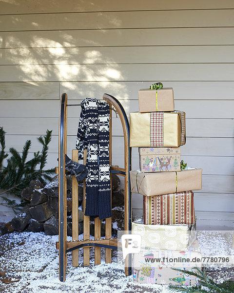 Schal  Holzschlitten und Weihnachtsgeschenke auf verschneiter Veranda