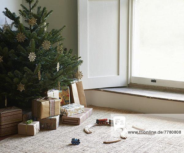 Zugpackung und Weihnachtsgeschenke unter dem Baum