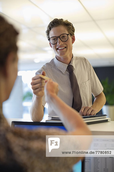 Geschäftsleute beim Kartentausch im Büro