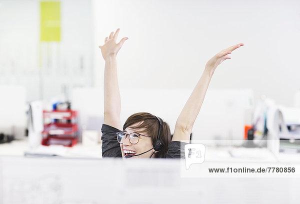 Geschäftsfrau im Headset jubelnd am Schreibtisch
