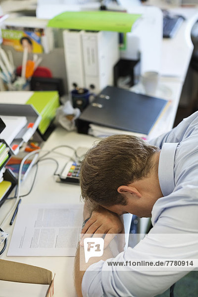 Geschäftsmann ruht Kopf auf Schreibtisch
