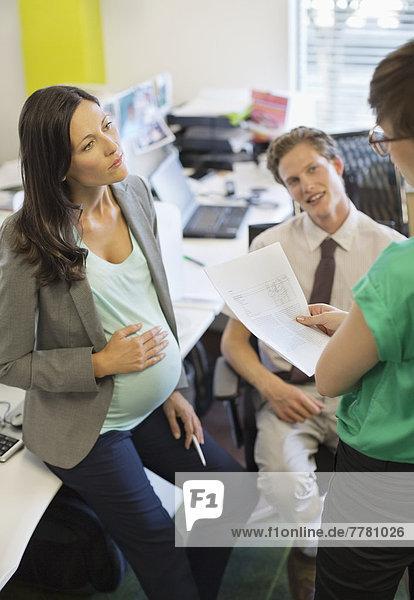 Schwangere Geschäftsfrau im Gespräch mit Kollegen
