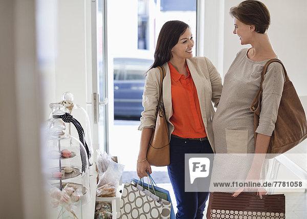 Lächelnde Frauen beim gemeinsamen Einkaufen