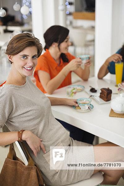 Schwangere Frau bei einer Tasse Kaffee mit Freunden