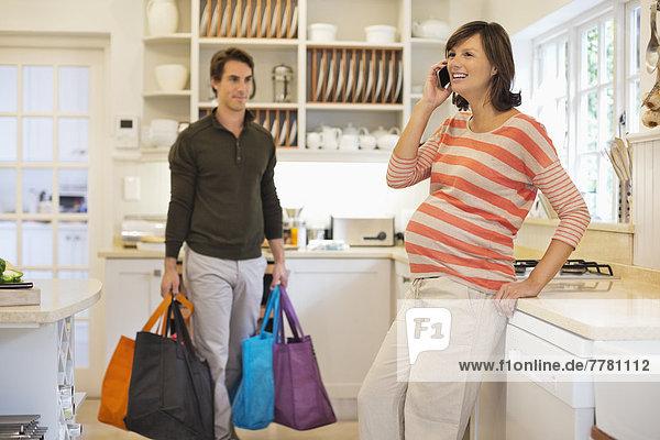 Mann trägt Taschen für schwangere Freundin