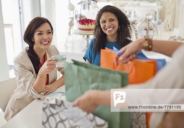 Frau zeigt Freunden Einkaufstaschen
