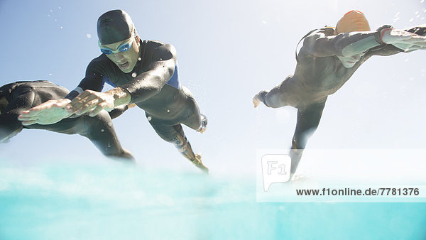 Triathleten in Trikots,  die in den Ozean laufen.