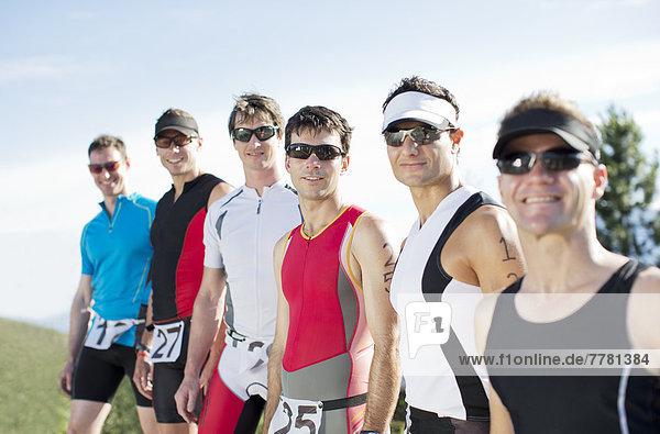 Läuferinnen und Läufer lächeln gemeinsam im Freien