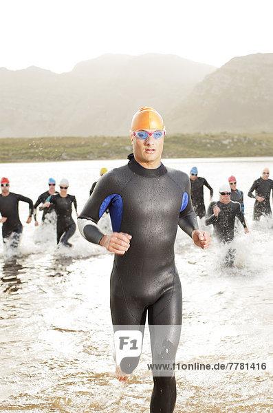 Triathleten im Trikostüm im Wellenlauf