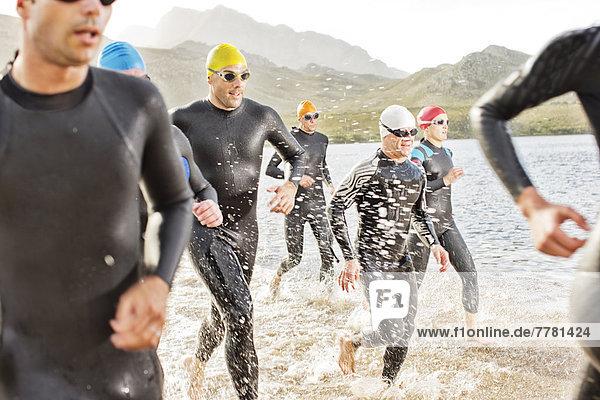 Triathleten in Trikots gehen in Wellen