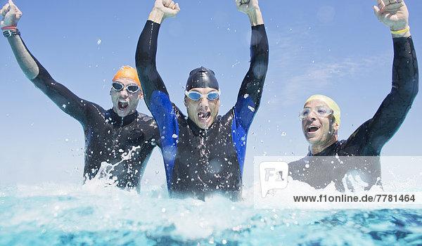 Triathleten in Trikots  die in Wellen spritzen