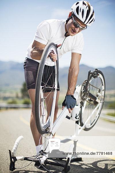 Mann beim Einstellen des Fahrrads auf der Landstraße