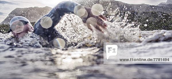 Triathleten schwimmen im Rennen