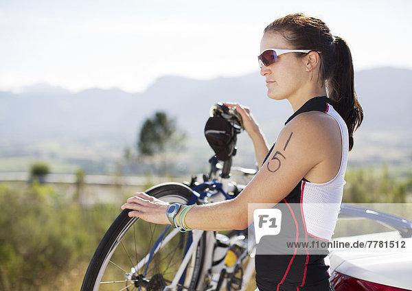 Frau stehend mit Fahrrad im Freien