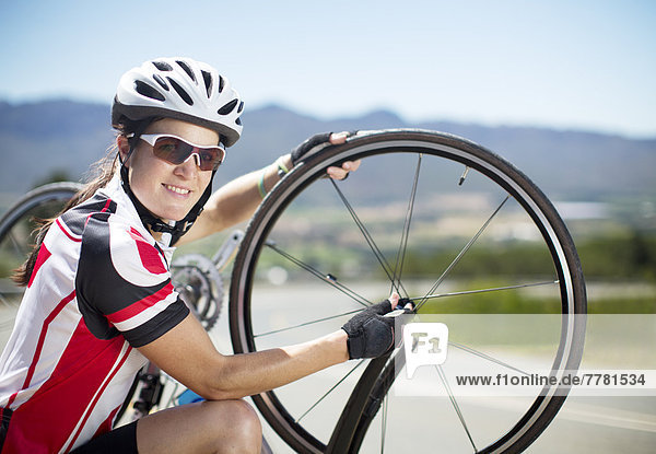 Radfahrer beim Einstellen der Reifen auf der Landstraße