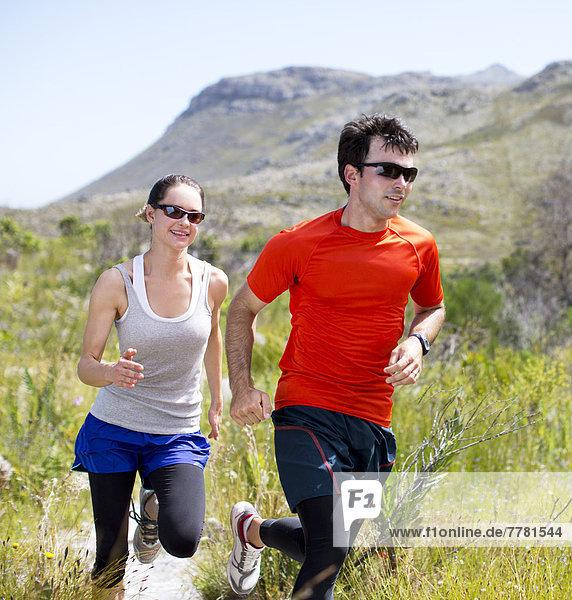 Paar läuft auf Schmutzbahn