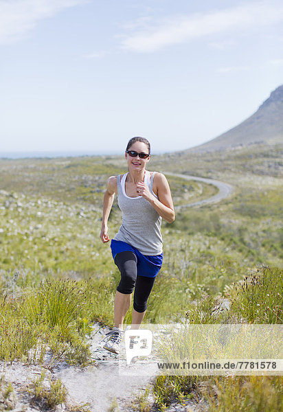 Frau läuft auf dem Feldweg