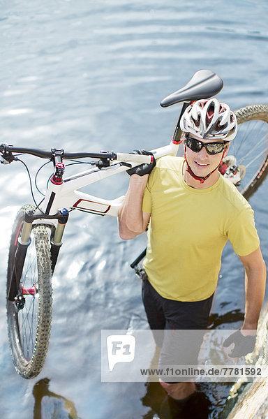 Mann mit Mountainbike im Fluss