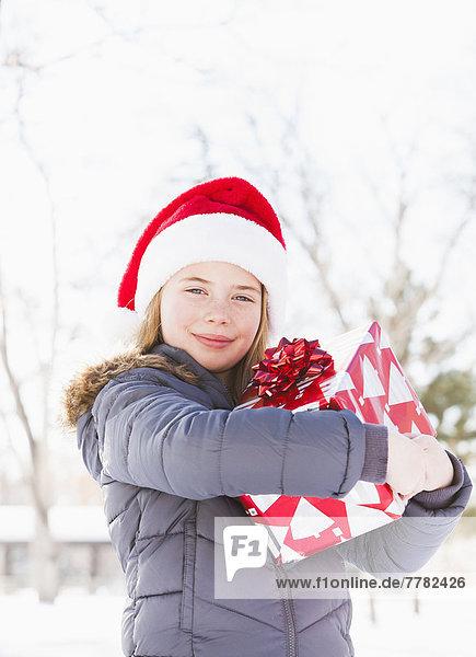 Caucasian girl in Santa hat holding Christmas present