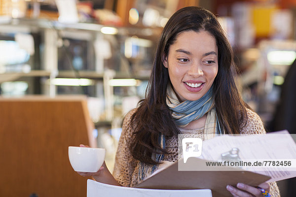 Mixed race woman reading clipboard in coffee shop