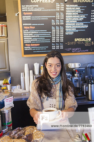 Mixed race woman working in coffee shop
