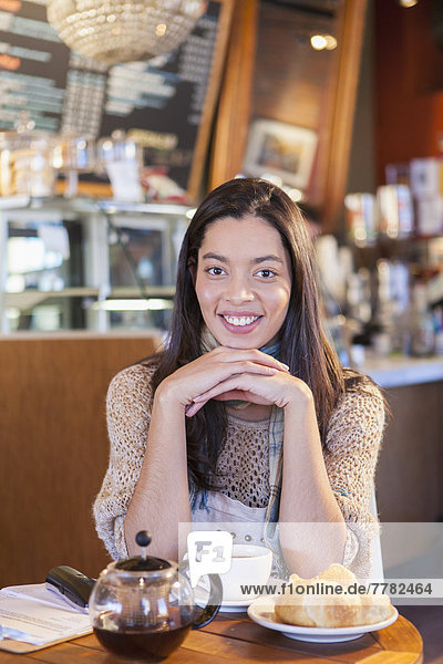 Mixed race woman sitting in coffee shop