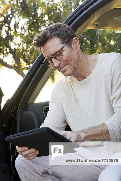 Caucasian man using digital tablet in car