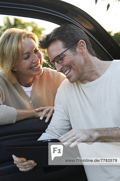 Caucasian couple using digital tablet by car