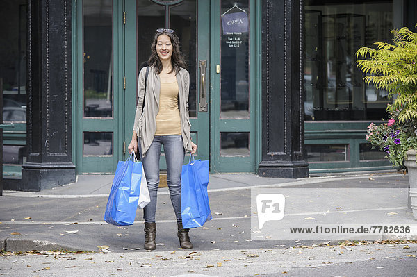 Mixed race woman carrying shopping bags