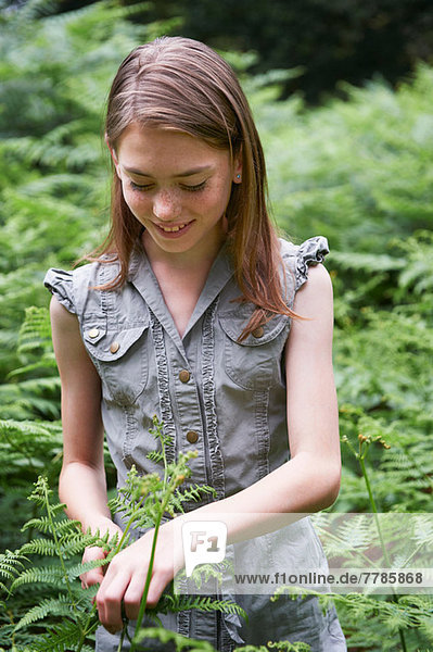 Teenage girl touching bracken in forest