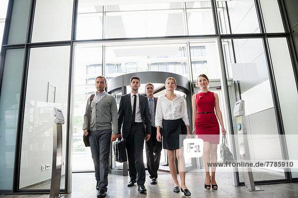 Gruppe von Geschäftsleuten  die in ein gläsernes Bürogebäude gehen.