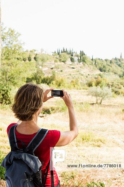 Frau fotografiert die ländliche Szene mit dem Fotohandy
