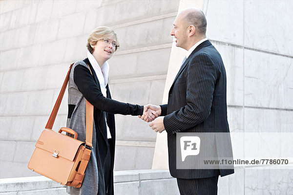 Geschäftsfrau und Mann beim Händeschütteln
