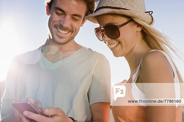 Junges Paar schaut auf Smartphone