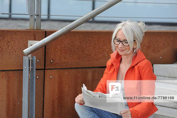 Seniorin beim Zeitungslesen auf der Treppe